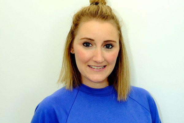 A headshot of Shelley who has blonde shoulder length hair and fair skin